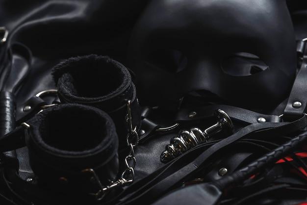 Seks bdsm z dominacją i uległością. skórzany bat flogger, kajdanki i maska na czarnym tle