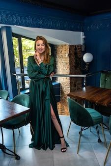 Seksowna atrakcyjna młoda kobieta ubrana w zieloną długą sukienkę pozowanie na krześle w miejskiej kawiarni