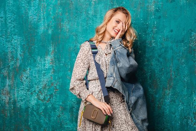 Seksowna atrakcyjna stylowa blondynka w dżinsach i kurtce oversize idąca przed zieloną ścianą na ulicy