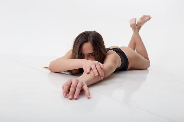 Seksowna azjatka z długimi włosami pozowanie w czarnej bieliźnie na tle białego studia z bosymi stopami. atrakcyjna kobieta leży na podłodze na brzuchu. modelowe testy chudej pani w body