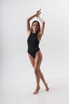 Seksowna azjatka z długimi włosami pozowanie w czarnej bieliźnie na tle białego studia z bosymi stopami. atrakcyjna kobieta stojąca na podłodze na palcach. modelowe testy chudej pani w body