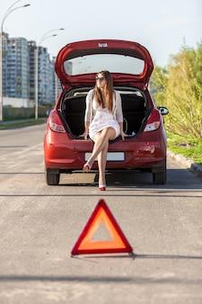 Seksowna bezradna kobieta siedząca w pobliżu zepsutego czerwonego samochodu