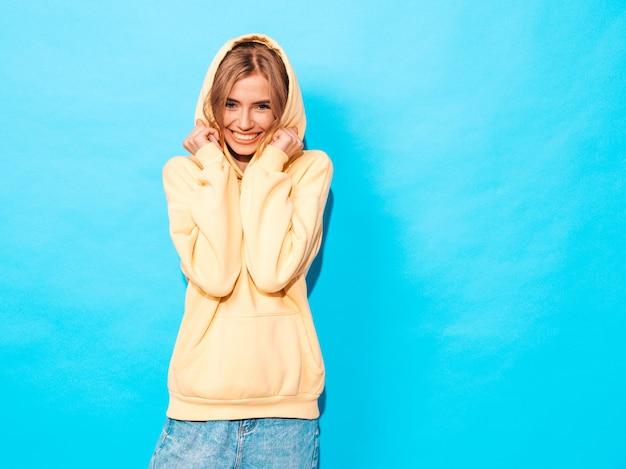 Seksowna beztroska kobieta pozuje blisko błękit ściany. pozytywny model zabawy