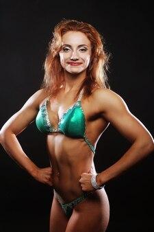 Seksowna blond kulturysta kobieta w bikini na czarnej ścianie