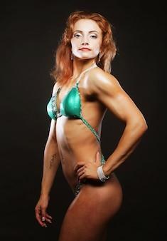 Seksowna blond kulturysta kobieta w bikini na czarnym tle