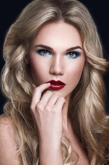 Seksowna blondynka modelka. długie kręcone blond włosy i makijaż