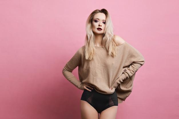 Seksowna blondynka modelka o niebieskich oczach, idealnym ciele i jasnym makijażu, w czarnej stylowej bieliźnie i fascynującej bluzie pozuje na różowym tle