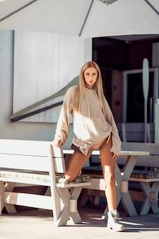 Seksowna blondynka w beżowej bieliźnie i płaszczu pozowanie w pobliżu kawiarni. odpoczynek i przyjemność.