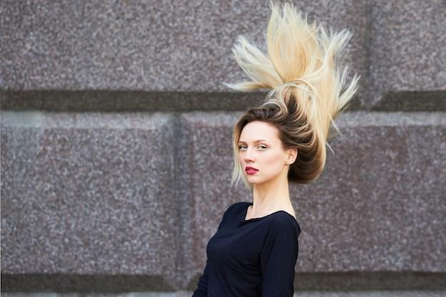 Seksowna blondynka w czarnej sukience. z rozwianymi włosami o kamienną ścianę. w dowolnym celu.