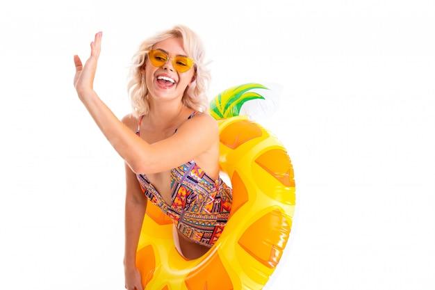 Seksowna blondynka w okularach z nadmuchiwanym kółkiem w formie ananasa macha ręką w lewo