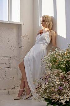 Seksowna blondynka w pięknej białej sukni stoi w pobliżu okna przed bukietem dzikich kwiatów. romantyczna dziewczyna z pięknym naturalnym makijażem