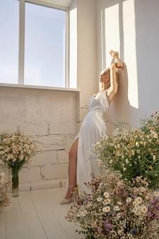 Seksowna blondynka w pięknej białej sukni stoi w pobliżu okna przed bukietem dzikich kwiatów