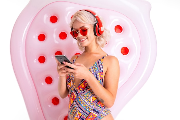 Seksowna blondynka w stroju kąpielowym i okularach przeciwsłonecznych ze smartfonem w dłoniach na tle materaca do pływania słucha muzyki na słuchawkach