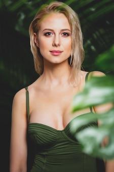 Seksowna blondynka w stroju kąpielowym w pobliżu liści palmowych