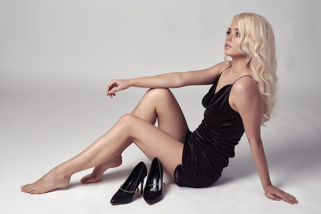 Seksowna blondynka w sukience pozowanie w studio