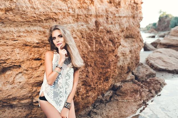 Seksowna blondynka z długimi włosami pozuje do kamery na tle rocka.