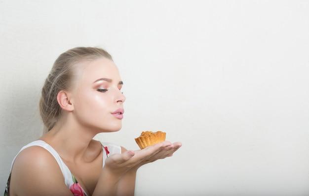 Seksowna blondynka z naturalnym makijażem trzymając pikantny deser z orzechami. miejsce na tekst