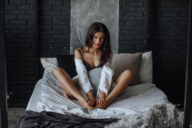 Seksowna brunetka dziewczyna na łóżku w bieliźnie na ciemnym tle