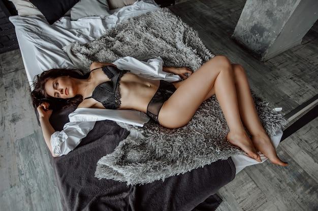 Seksowna brunetka dziewczyna w czarnej bieliźnie leżąc na łóżku
