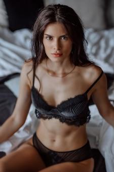 Seksowna brunetka dziewczyna w czarnej bieliźnie siedzi na łóżku