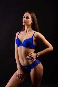 Seksowna brunetka kobieta o długich ciemnych włosach w niebieskiej bieliźnie, odizolowana na ciemnoszarym tle