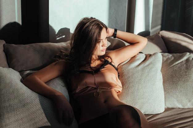 Seksowna brunetka kobieta pozuje w eleganckiej bieliźnie, patrząc na kamerę dziewczynę z idealnym ciałem leżącym