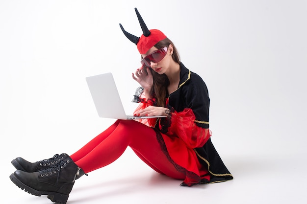 Seksowna brunetka kobieta w czerwone rajstopy, czarne buty i rogi diabła za pomocą laptopa