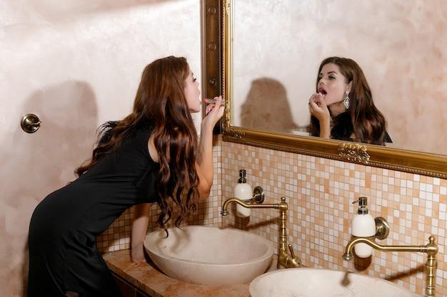 Seksowna brunetka kobieta w małej czarnej sukience siedzi na umywalce. noir, namiętny, włoski. dziewczyna się śmieje, uśmiech