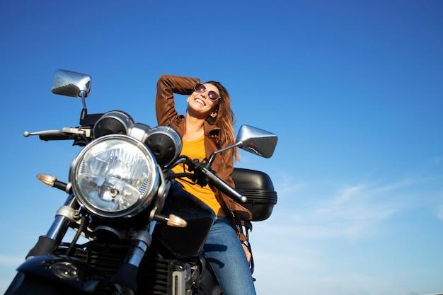 Seksowna brunetka kobieta w skórzanej kurtce siedzi na motocyklu w stylu retro w piękny słoneczny dzień
