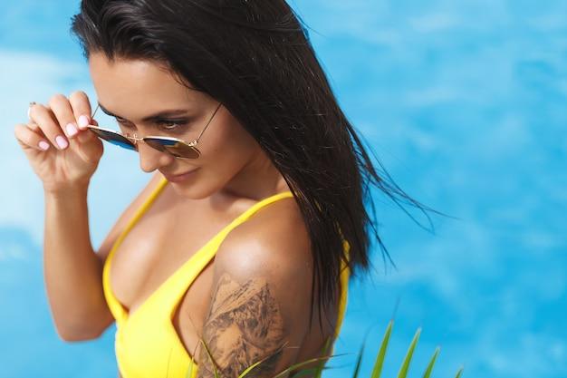 Seksowna brunetka kobieta ze złotą opalenizną i tatuażem, ubrana w bikini z okularami przeciwsłonecznymi, relaks przy basenie.