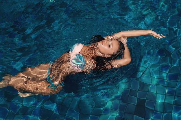 Seksowna brunetka pozuje w basenie z zamkniętymi oczami