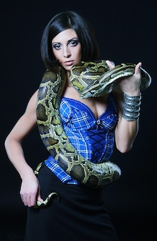 Seksowna brunetka trzyma pythona na czarnym tle