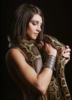 Seksowna brunetka trzyma pytona na czarno