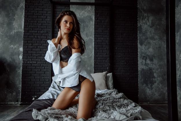 Seksowna brunetka w bieliźnie klęczy na łóżku