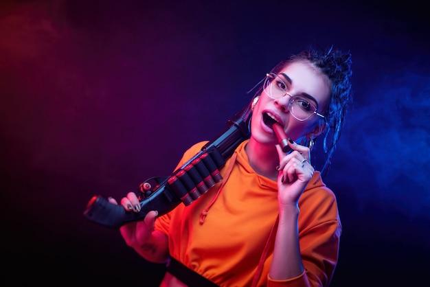 Seksowna brunetka w pomarańczowym kombinezonie ze strzelbą na ciemnym tle w neonowym świetle