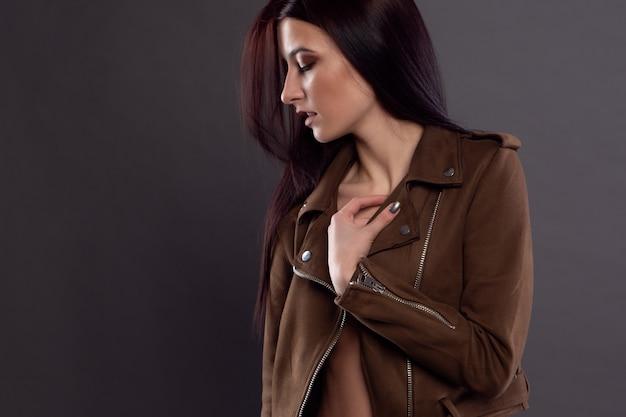 Seksowna brunetka w rozpiętej kurtce, ubrana na piękne ciało.