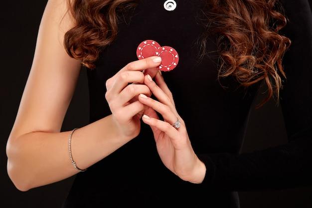 Seksowna brunetka z kręconymi włosami pozuje z żetonami w dłoniach, koncepcja pokera czarne tło