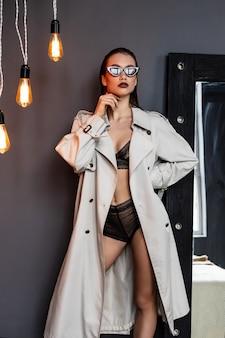 Seksowna brunetki dziewczyna jest ubranym trencz i bieliznę