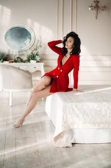 Seksowna brunetki dziewczyna w czerwonym blezerze uwodzicielski pozuje przy łóżkiem.