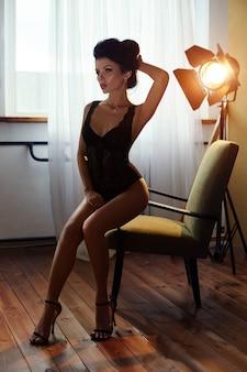 Seksowna brunetki kobieta siedzi na krześle w bieliźnie w domu. idealna figura, piękne ciało na kobiecie. gładka czysta skóra i długie mocne włosy. kobieta w świetle żółtej lampy
