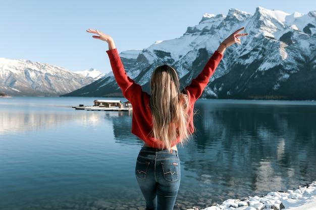 Seksowna dama o szczupłym, idealnym ciele stojąca na plaży w pobliżu zimowego jeziora. biały śnieg leżący na ziemi i na szczytach gór. długie blond włosy leżące z tyłu czerwonego swetra.