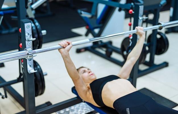 Seksowna, dopasowana dziewczyna leżąca na specjalnym symulatorze i robi ćwiczenia push-up ze sztangą