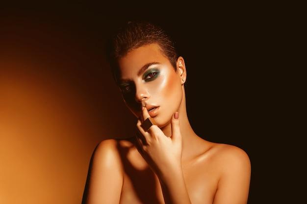 Seksowna dorosła kobieta z profesjonalnym zielonym makijażem i krótką fryzurą brunetki