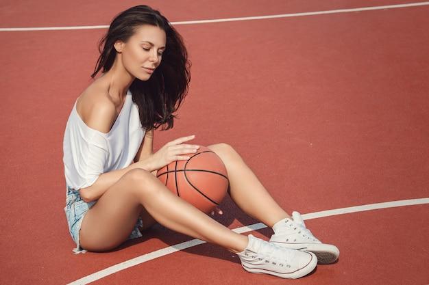 Seksowna dziewczyna na boisko do koszykówki