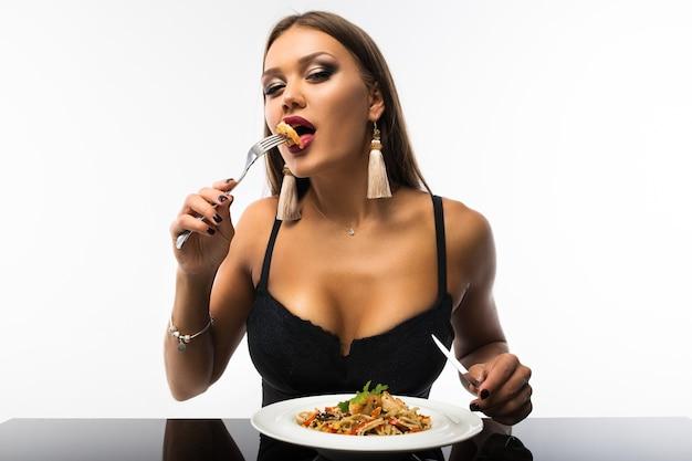 Seksowna dziewczyna przy równym stole z widelcem i nożem w dłoniach. na stole talerz z makaronem i krewetkami.