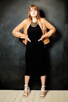 Seksowna dziewczyna. rude włosy. czarna sukienka. skórzana kurtka