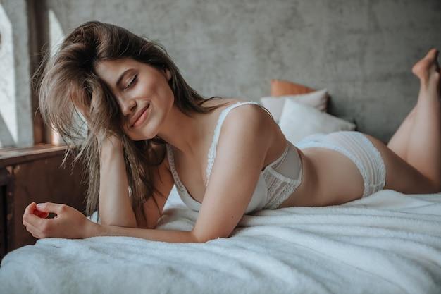 Seksowna dziewczyna w białej bieliźnie na łóżku