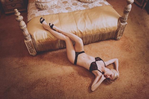 Seksowna dziewczyna w bieliźnie pozuje przy pokojem hotelowym. uroda i moda