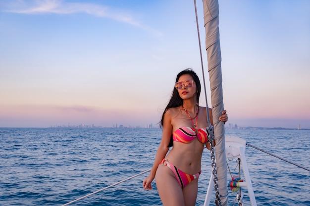 Seksowna dziewczyna w bikini pozuje na łodzi przy morzem