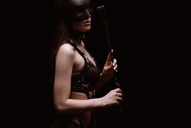 Seksowna dziewczyna w czarnym pięknym biustonoszu bawiąc się batem. koncepcja bdsm